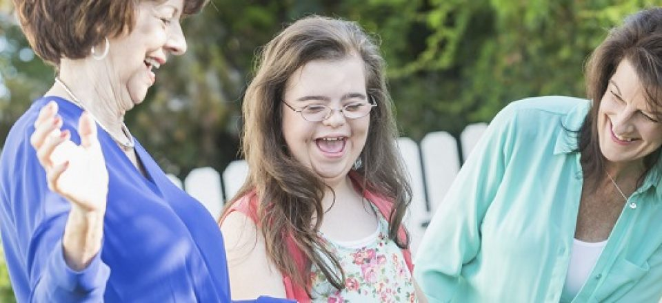 A teenager girl with down syndrome, laughing and having fun with her mother and grandmother outdoors in the back yard.  She is standing in the middle holding her grandmother's hand.