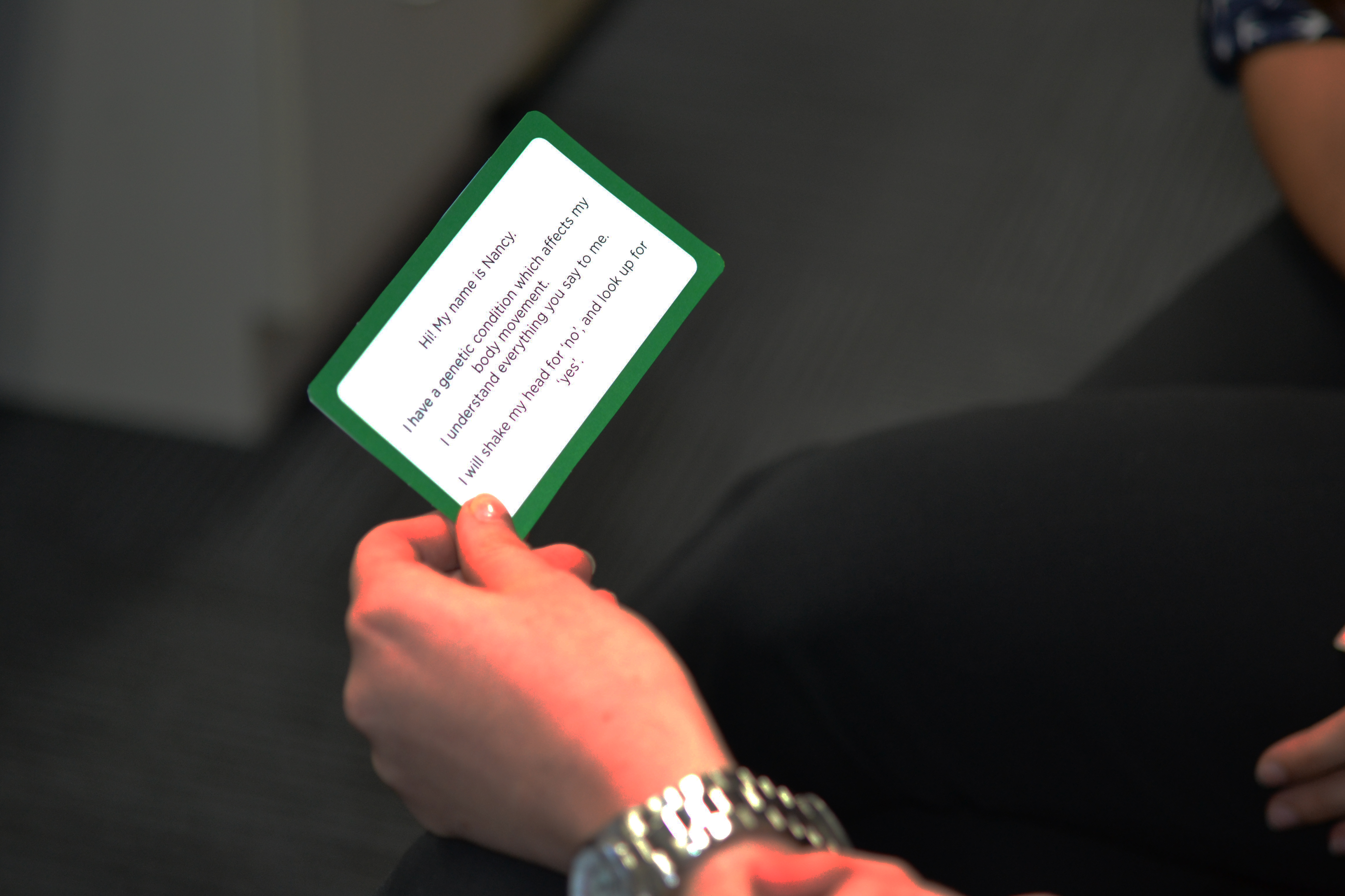 person holding an introduction card which indicates how they communicate
