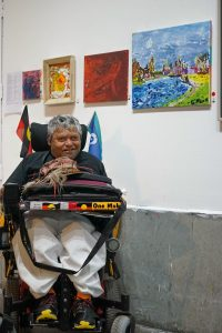 Photograph of Greg Muir in front of his artworks