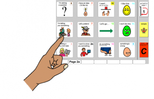 Finger pointing to an item on a PODD communication book