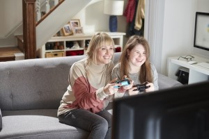 A mother and daughter are smiling while they play a video game together at home on their television.