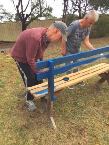 Housemates Tom and Anthony painting a bench bright primary blue.