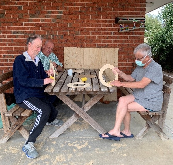 Tom, Stewart, and Anthony sitting on the cafe benches, sanding the noughts for the noughts and crosses game.