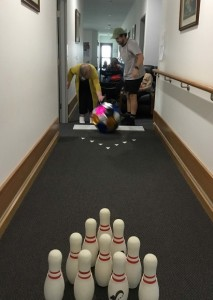 Christine is bowling a large, soft, shiny ball down her hallway, towards a set of indoor bowling pins. Three people are gathered behind her to watch her bowl.