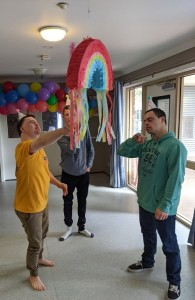 Nick, Craig, and Jacob are celebrating Nick's birthday, wearing party hats and standing around a rainbow piñata. A garland of colourful balloons has been hung along the wall behind them. Nick is using a stick to hit the piñata.