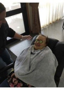 Kerri is relaxing in a chair with cucumber slices over her closed eyes. A person is applying a green face mask to Kerri's face. Kerri is wrapped in a soft blanket.