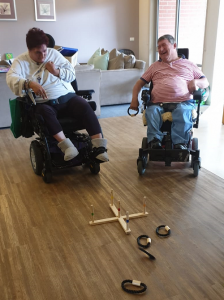 Angela and Cam are playing quoits in their home. They are using wheelchairs. Angela has just thrown her ring and missed the spikes. Cam is laughing and has his ring in his hand ready to take his turn next.