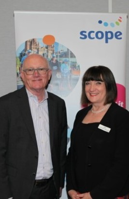 Arthur Rogers and Jennifer FItzgerald at Scope's 2018 AGM. They are standing in front of a banner with photos and the Scope logo in the top right corner. They are both smiling at the camera.