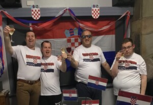 Four men are raising their wine glasses in a toast. They are wearing tee shirts with the Croatian flag. The room is decorated with the flag and streamers in the flag colours of red, white, and blue. In front of them is a dining table decorated with mini flags and a sticker that says 'I love Croatia'.