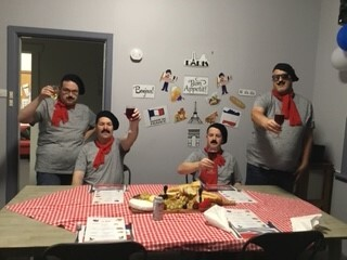 Four men are raising their wine glasses in a toast. The two men in the middle are sitting at the dining table, with a man standing either side of them. They are wearing red neck scarves, black berets and fake moustaches. The table is decorated like a French bistro with a red checked tablecloth. There is a cheese platter in the middle of the table.