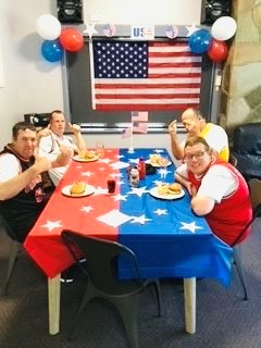 Four men are sitting at a dining table smiling for the camera sitting at a dining table decorated with a red and blue tablecloth with white stars. They are all wearing basketball jerseys. The room is decorated with a USA flag and balloons in the flag colours of red, white, and blue.